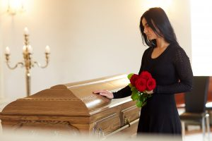 woman standing next to casket